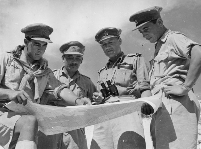 behind_the_el_alamein_front_officers_of_the_28th_battalion_studying_a_map_of_the_western_desert__23_octoher_1942__da06727f